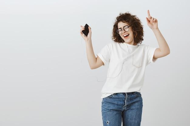Garota atraente e despreocupada dançando música no celular, ouvindo música em fones de ouvido