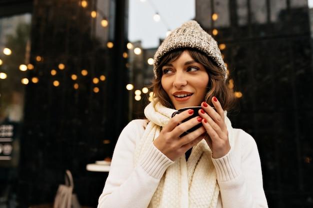 Garota atraente e elegante com suéter branco e boné de malha bebendo café do lado de fora no fundo da cidade com luzes. foto de alta qualidade