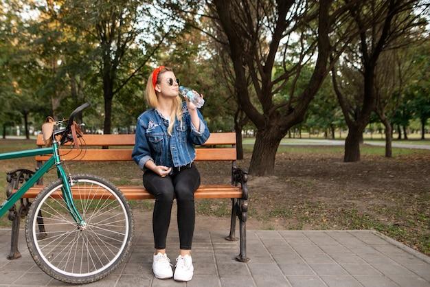 Garota atraente e elegante, sentado num banco de um parque perto de uma bicicleta com uma garrafa de água nas mãos dela
