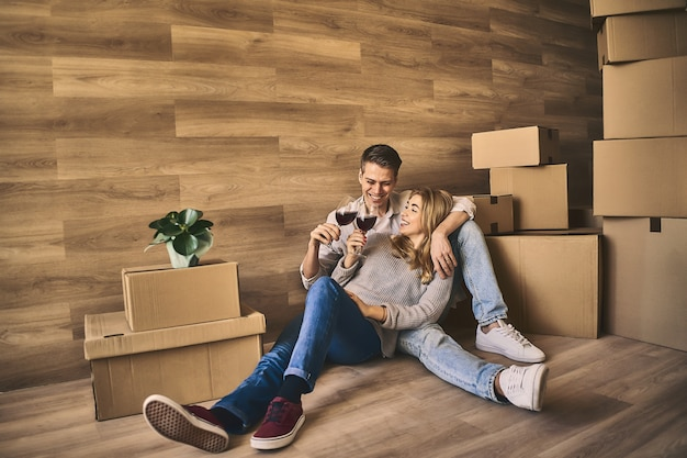 Garota atraente e homem bonito se preparando para comemorar a mudança para um novo apartamento