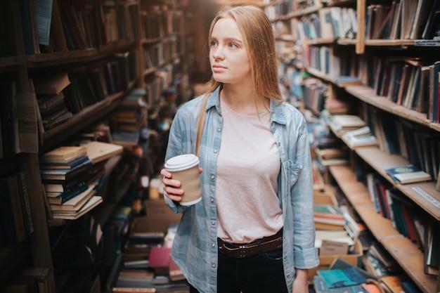 Garota atraente e legal está de pé entre estantes grandes e longas, com livros antigos. ela está segurando uma xícara de café na mão e olhando para a prateleira. a mulher está procurando um livro.