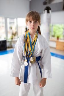 Garota atraente e talentosa vestindo quimono e medalhas pela vitória