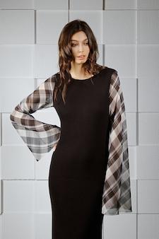 Garota atraente em acolhedor vestido de lã colorido de malha