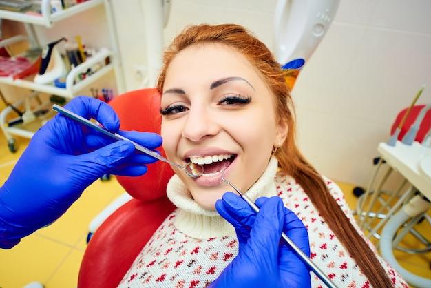 Garota atraente em cadeira odontológica vermelha na recepção de dentistas