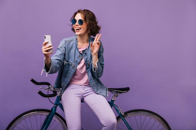 Garota atraente em calças roxas fazendo selfie. bem-humorada jovem de jaqueta jeans, sentada na bicicleta.