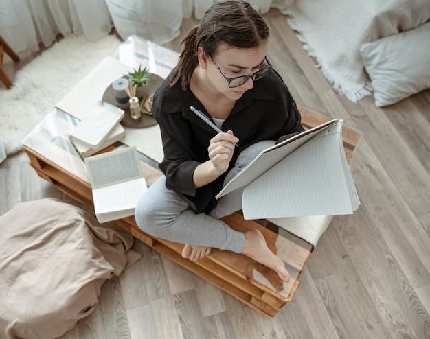 Garota atraente em casa sentada com um caderno e uma caneta entre a vista superior de livros.