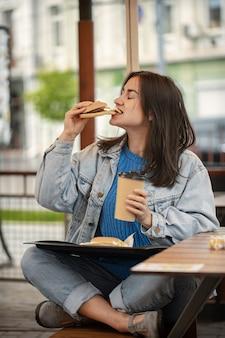 Garota atraente em estilo casual come um hambúrguer com café sentado na esplanada de verão.