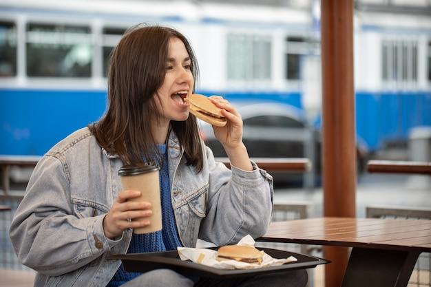 Garota atraente em estilo casual está desfrutando de fast food sentado no terraço de verão.
