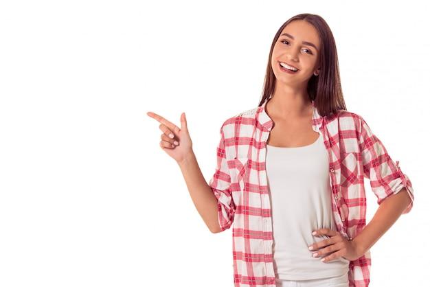 Garota atraente em roupas casuais está apontando para o lado.