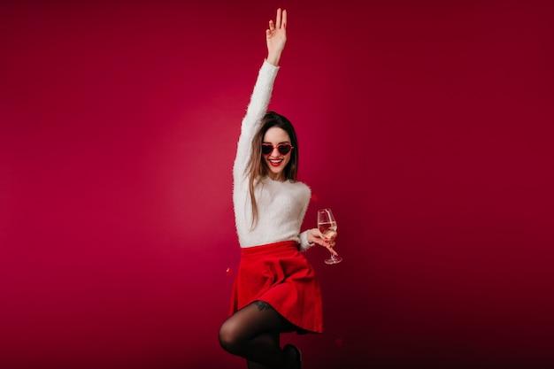 Garota atraente em saia vermelha curta engraçada dançando com um copo de vinho na mão