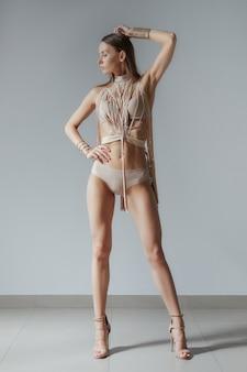 Garota atraente em traje de banho moda com fitas