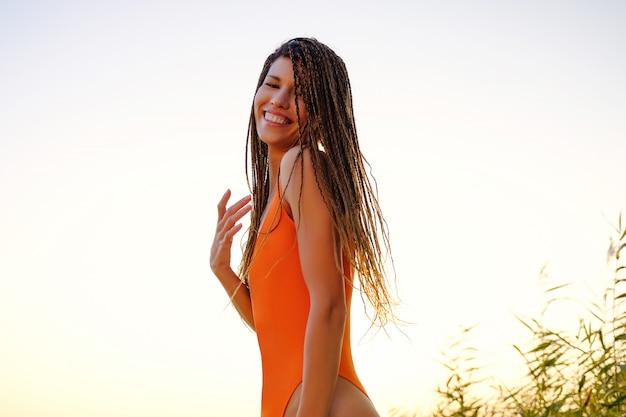 Garota atraente em traje de banho na praia ao nascer do sol