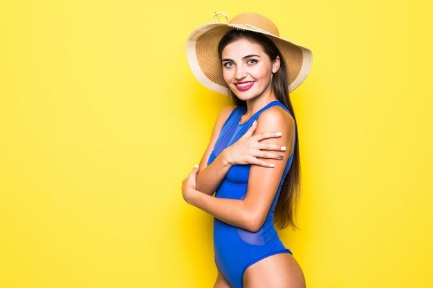 Garota atraente em um biquíni branco, chapéu, óculos de sol, emocionalmente abriu a boca em uma parede amarela com um corpo perfeito. isolado.
