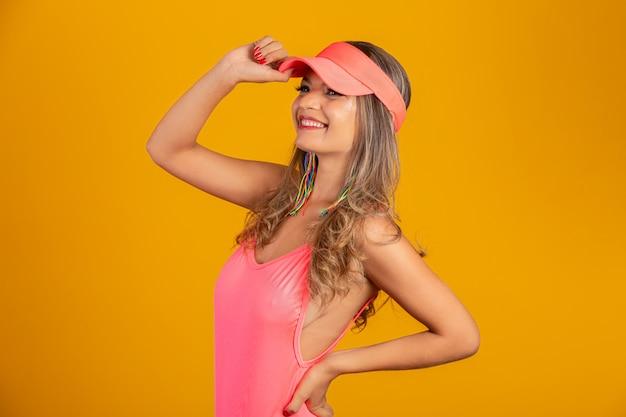 Garota atraente em um biquíni rosa, chapéu, emocionalmente abriu a boca em uma parede amarela brilhante com um corpo perfeito. isolado.