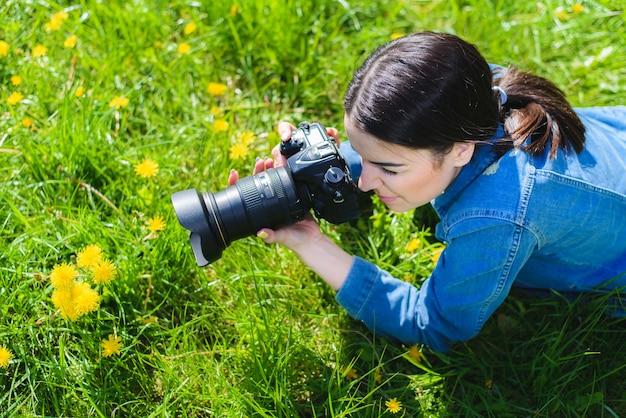 Garota atraente em um prado tira fotos de flores