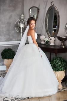 Garota atraente em um vestido de noiva branco fica em um espelho