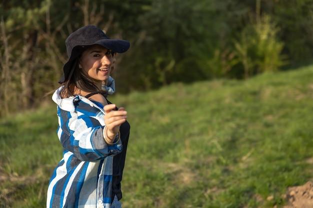 Garota atraente em uma caminhada na floresta de primavera em estilo casual.