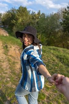 Garota atraente em uma caminhada na floresta de primavera em estilo casual