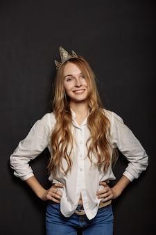 Garota atraente em uma camisa branca com uma coroa na cabeça