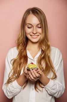 Garota atraente em uma camisa branca está segurando cupcakes