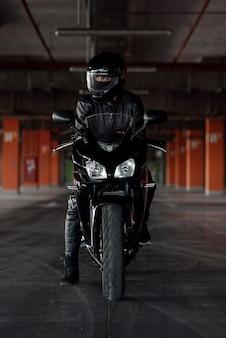 Garota atraente em uniforme protetor preto, luvas e capacete integral, andando em sua motocicleta no estacionamento subterrâneo.