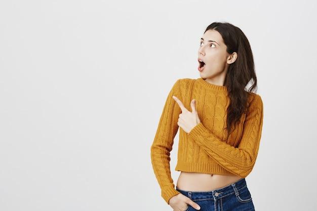 Garota atraente espantada e impressionada com o queixo caído, apontando para o canto esquerdo superior