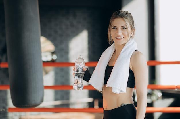 Garota atraente esporte sorrindo e bebendo água em pé na aula de fitness