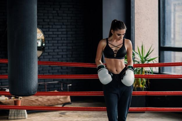 Garota atraente esportes caucasiana inclinou-se sobre as cordas no ringue de boxe, descansar após treino intensivo no ginásio moderno.