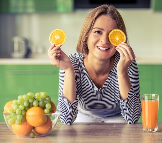 Garota atraente está cobrindo os olhos com fatias de laranja.
