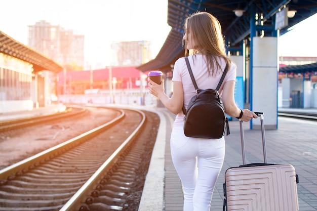Garota atraente está de pé com bagagem na estação e esperando o trem, o aluno está indo em uma viagem, ela está caminhando ao longo da plataforma com café, cópia espaço