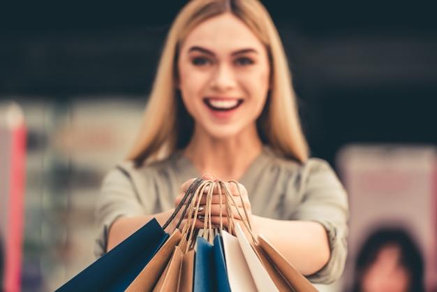 Garota atraente está segurando sacolas de compras.