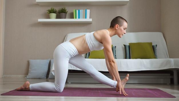 Garota atraente está sentado no chão em uma pose de yoga, praticando relaxamento e meditação