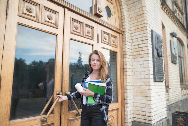 Garota atraente estudante com livros nas mãos fica na porta da universidade e olha para a câmera.