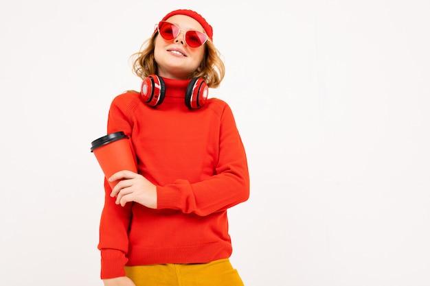 Garota atraente europeia com fones de ouvido e óculos de sol e um copo de café na mão