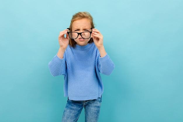 Garota atraente europeu olha através de óculos na parede de luz azul