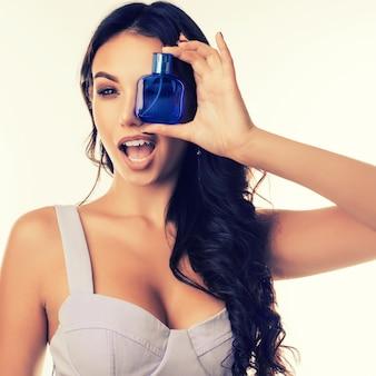 Garota atraente fecha o olho com um frasco de perfume piscando o outro olho.