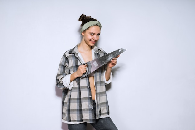 Garota atraente feliz em uma camisa xadrez segurando uma serra de metal afiada, fazendo reparos