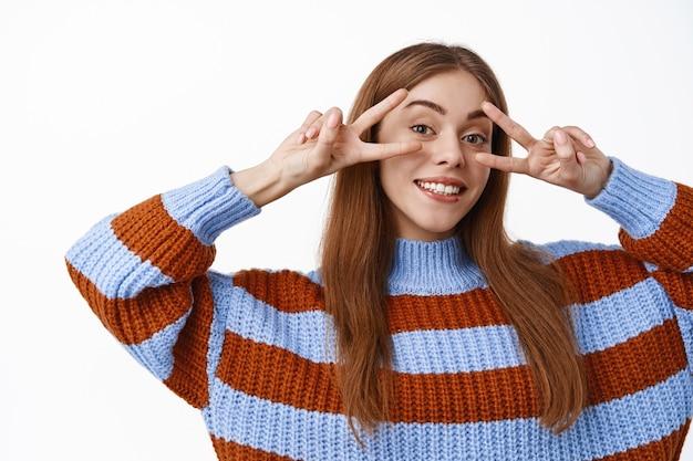 Garota atraente feliz mostrando sinais v da paz sobre os olhos, sorrindo com dentes perfeitos, parada relaxada e despreocupada, em pé sobre uma parede branca