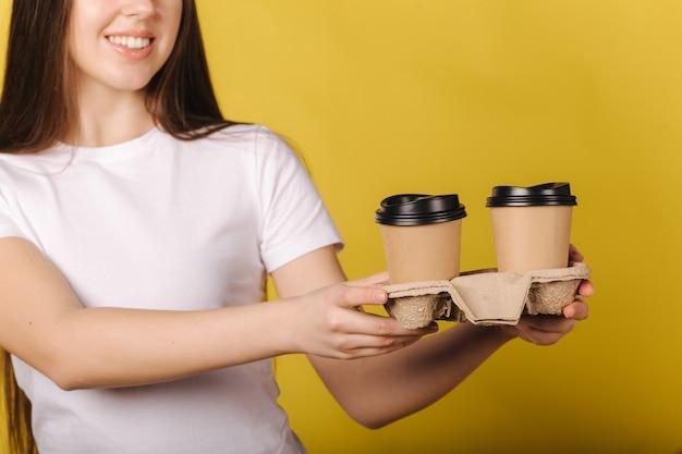 Garota atraente feliz segurando duas xícaras de café e sorrindo, mulher de camiseta branca