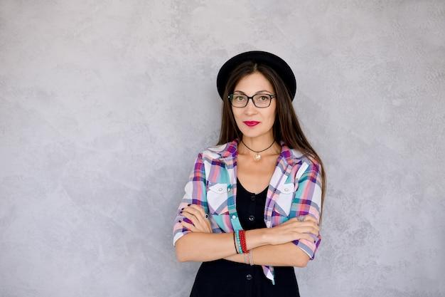 Garota atraente hipster de óculos e chapéu