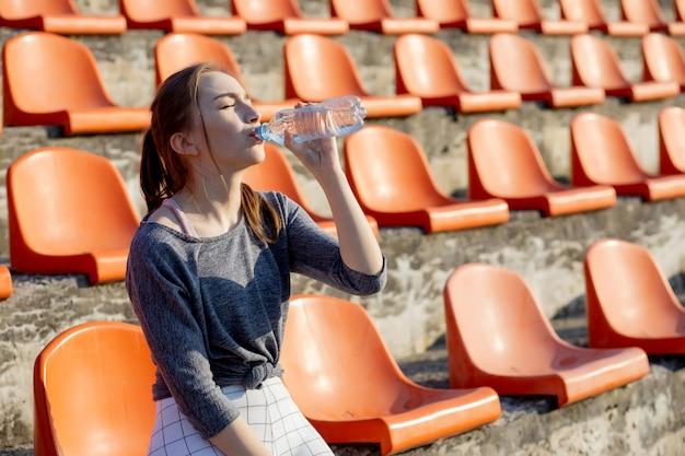 Garota atraente jovem desportiva no sportswear relaxante após treino duro sentar e beber água de garrafa de esporte especial depois de correr