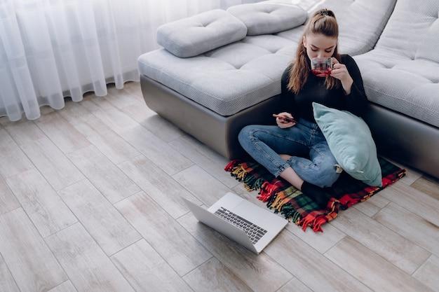 Garota atraente jovem em casa trabalhando com um laptop e falando ao telefone. conforto e aconchego em casa. escritório em casa e trabalho em casa. emprego on-line remoto.