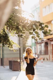 Garota atraente loira em óculos de sol com o telefone no sol quente de verão