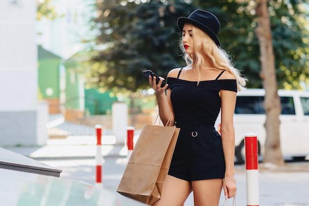 Garota atraente loira em um chapéu depois de fazer compras nos raios do sol de verão