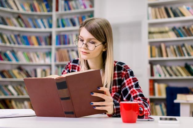 Garota atraente loira inteligente jovem estudante de óculos, sentado à mesa, concentrada ao ler o livro na biblioteca da universidade. estante de livros com diferentes livros no espaço