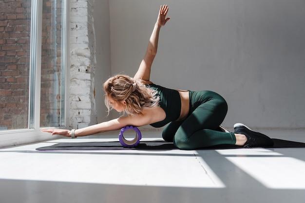 Garota atraente magro com cabelo loiro ondulado, usando o rolo de espuma para relaxar os músculos dos braços após o treino. jovem apta a mulher com roupas esportivas verdes, massageando o corpo no tapete de ioga preto.