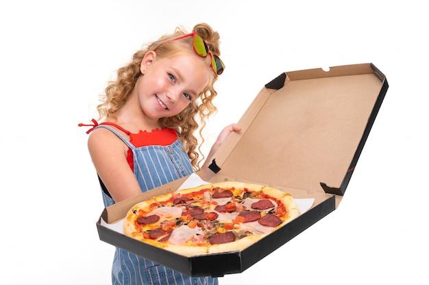 Garota atraente mantém uma caixa aberta com pizza na parede branca