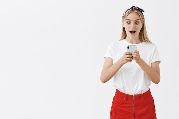 Garota atraente moderna usando telefone celular e parecendo surpresa