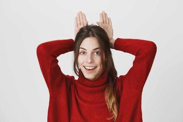 Garota atraente mostra orelhas de coelho atrás da cabeça