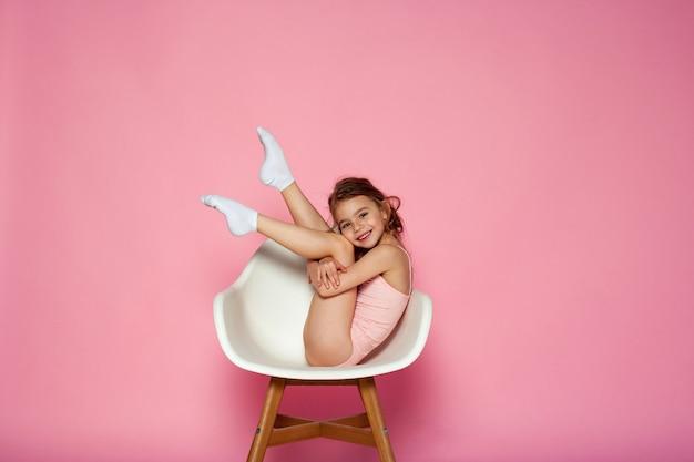 Garota atraente na cadeira branca no fundo rosa